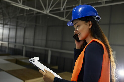 Smiling female worker on the phone in factory warehouse - ZEDF02241