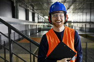 Portrait of happy worker in factory warehouse - ZEDF02247