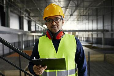 Portrait of worker holding clipboard in factory warehouse - ZEDF02253