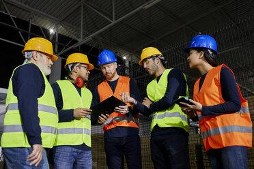 Workers standing in factory warehouse talking - ZEDF02256