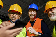 Happy workers in factory warehouse talking and using tablet - ZEDF02259