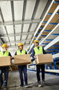 Three workers carrying boxes in factory warehouse - ZEDF02265