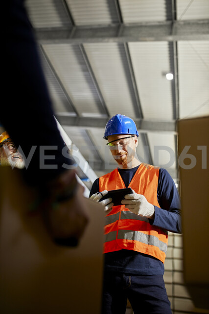 Worker in factory warehouse using tablet - ZEDF02277