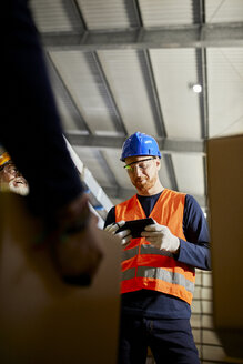 Worker in factory warehouse using tablet - ZEDF02277