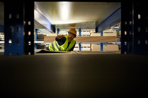 Worker with torch searching something in factory warehouse - ZEDF02280