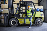 Portrait of confident mature worker at forklift in factory - ZEDF02286