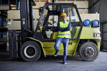 Portrait of confident worker at forklift in factory - ZEDF02289