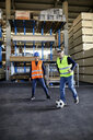 Workers playing football in factory warehouse - ZEDF02292