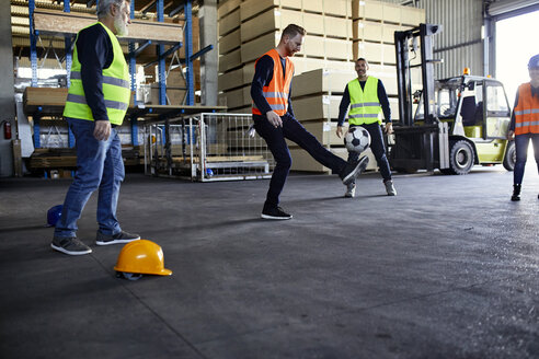 Workers playing football in factory warehouse - ZEDF02295