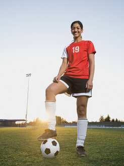 Mixed race woman posing with soccer ball - BLEF00067