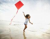 Mixed race girl running with kite on beach - BLEF00099