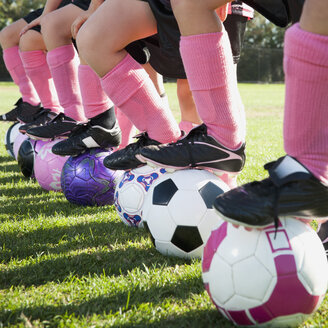 Girl soccer players standing with feet on soccer balls - BLEF00105