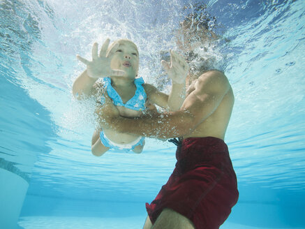 Mixed race father holding daughter in swimming pool - BLEF00114