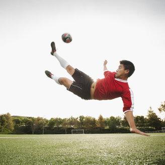 Asian soccer player in mid-air kicking soccer ball - BLEF00123