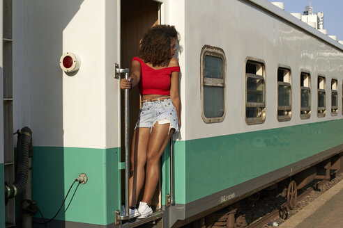Woman standing at the door of a train looking around - VEGF00045
