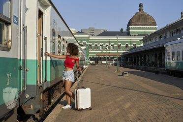 Woman with suitcase at train station getting into train - VEGF00048