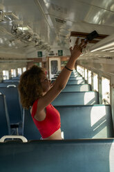 Young woman placing her suitcase in a train - VEGF00054