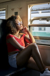 Young woman on a train looking out of window - VEGF00057