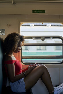 Young woman on a train checking her phone - VEGF00060