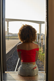 Woman sitting at the back door of a train looking out - VEGF00063