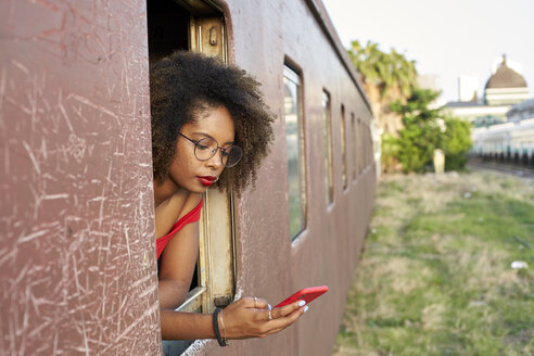 Young woman checking her phone at the window of a train - VEGF00066