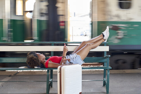 Woman with suitcase lying on a bench at the train station - VEGF00069