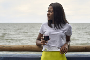 Portrait of young woman with glass of red wine in front of the sea - VEGF00075