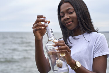 Portrait of young woman in front of the sea sending message in a bottle - VEGF00081