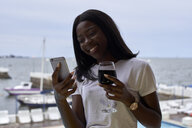 Portrait of happy young woman with glass of red wine looking at mobile phone - VEGF00090