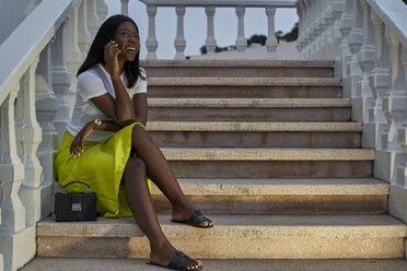 Portrait of smiling young woman on the phone sitting on stairs outdoors - VEGF00093