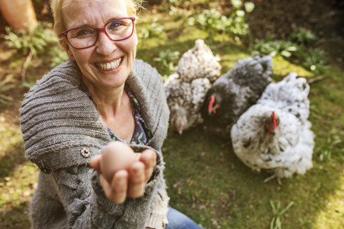 Portrait of happy woman in garden with her Orpington hens showing egg - JATF01138