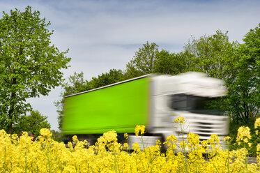 Truck in motion behind rape field - FRF00820