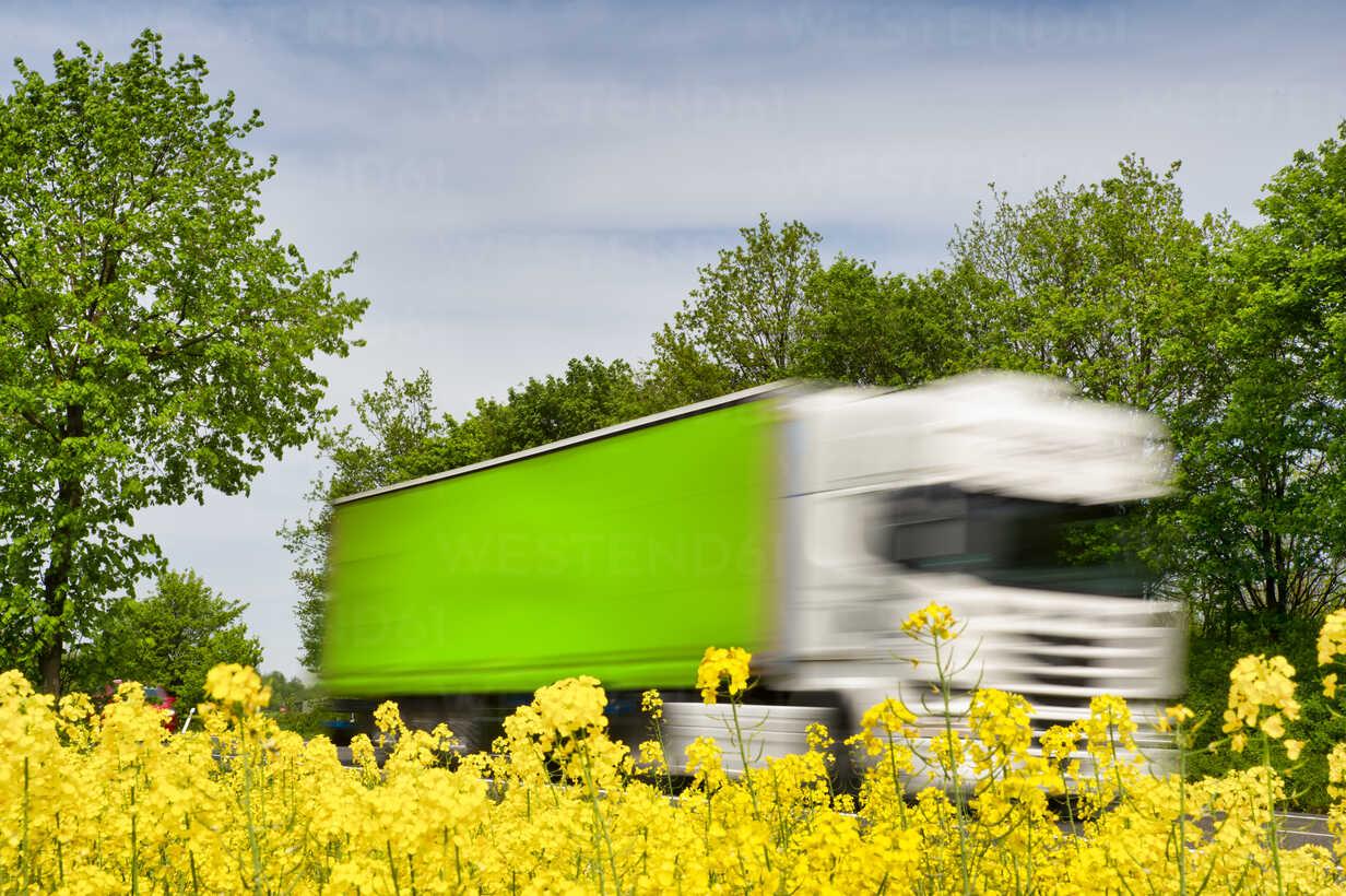 Truck in motion behind rape field - FRF00820 - Frank Röder/Westend61
