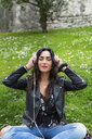 Young woman with white headphones, wearing black leather jacket - MGIF00387
