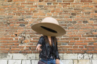 Portrait of young woman wearing black leather jacket, brick wall, throwing hat - MGIF00390