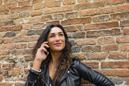 Portrait of young woman wearing black leather jacket, using smartphone, brick wall in the background - MGIF00393