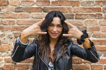 Portrait of young woman wearing black leather jacket and showing rock and roll sign, brick wall - MGIF00396