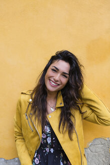 Portrait of young woman wearing yellow leather jacket, hand in hair - MGIF00402