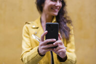 POrtrait of young woman wearing yellow leather jacket and taking a selfie, yellow wall in the background - MGIF00405