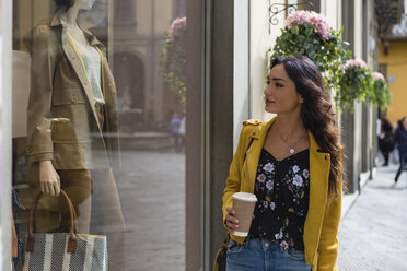 Portrait of young woman wearing yellow leather jacket, holding cup of coffee during shopping - MGIF00408