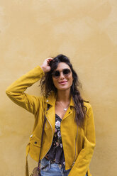 Portrait of young woman wearing yellow leather jacket and sun glasses - MGIF00411