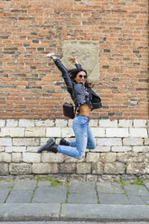 Young woman jumping in the air, brick wall in the background - MGIF00414