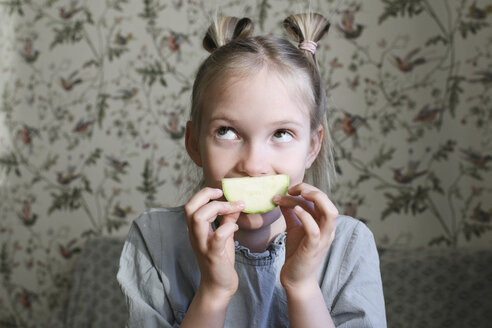 Russia, Moscow, smiling girl with piece of vegetable (squash) - EYAF00177