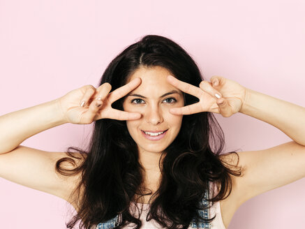 Portrait of young smiling woman with black hair and hands on face, in front of pink background - HMEF00359