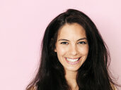 Portrait of young smiling woman with black hair in front of pink background - HMEF00362