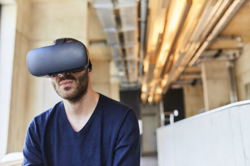Young man wearing VR glasses in modern office - FMKF05626