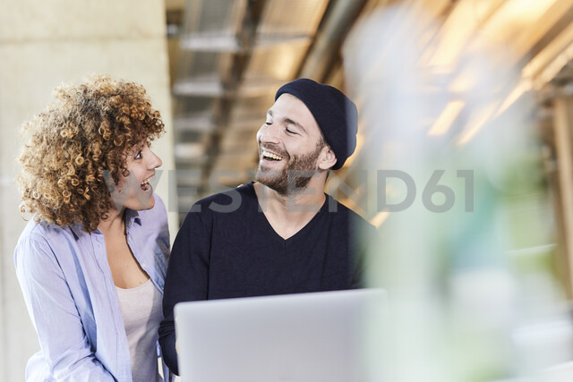 Excited man and woman with laptop in modern office - FMKF05635 - Jo Kirchherr/Westend61