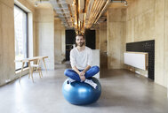 Portrait of young man sitting on fitness ball in modern office - FMKF05647