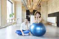 Portrait of man and woman with fitness ball in modern office - FMKF05653