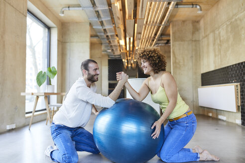 Happy man and woman arm wrestling on fitness ball in modern office - FMKF05656